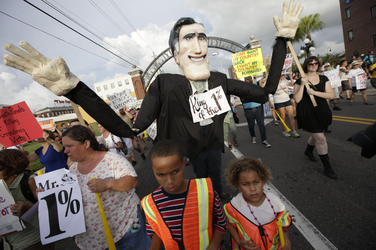 Demonstrators walk with a Mitt Romney type puppet during a protest march, Tuesday, Aug. 28, 2012, in Tampa, Fla. Protestors gathered in Tampa to march in demonstration against the Republican National Convention. (AP Photo/Dave Martin)