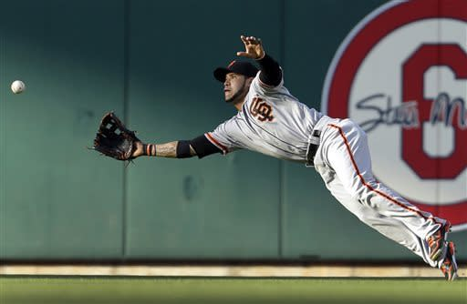 San Francisco Giants center fielder Gregor Blanco dives to catch a ball hit by St. Louis Cardinals' Ty Wigginton for an out during the second inning of the second game of a baseball doubleheader on Saturday, June 1, 2013, in St. Louis. (AP Photo/Jeff Roberson)