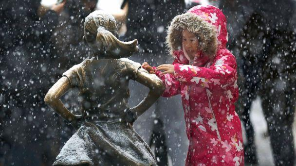 PHOTO: A young girl brushes off snow on the Fearless Girl statue in lower Manhattan on Thursday, Nov. 15, 2018, in New York. One of the first big storms of the season moved across the eastern half of the country on Thursday. (AP)