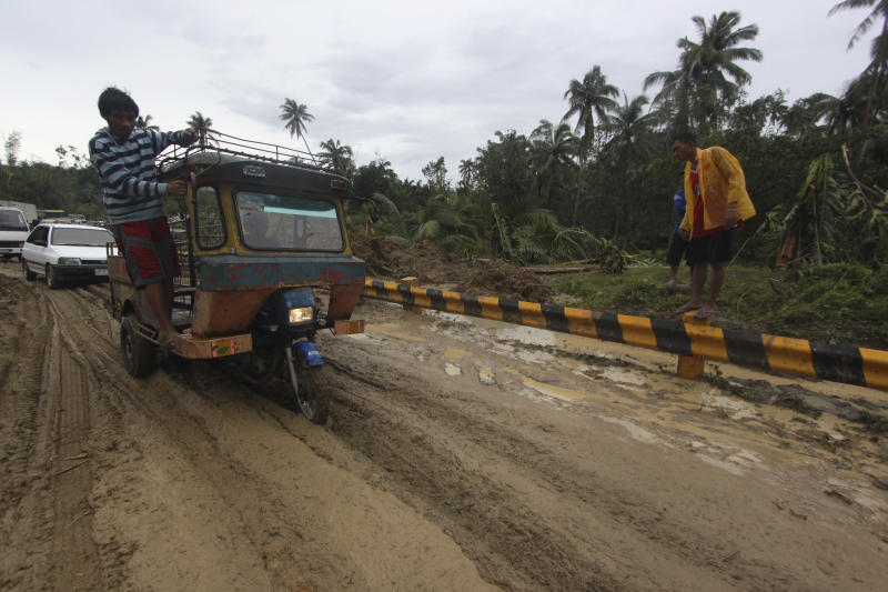 Commuters maneuver their vehicles through a muddy portion of a highway after Typhoon Bopha made a landfall in Compostela Valley in southeastern Philippines Tuesday Dec. 4, 2012. A Philippine governor says at least 33 villagers and soldiers have drowned when torrents of water dumped by the powerful typhoon rushed down a mountain, engulfing the victims and bringing the death toll from the storm to about 40. (AP Photo/Karlos Manlupig)