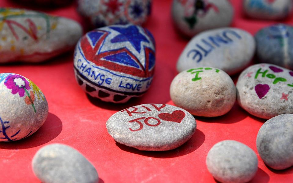 Children decorate pebbles as people attend a Great Get Together - Credit: Getty