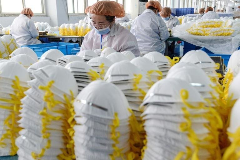 Workers produce face masks at a factory in Handan in China's northern Hebei province