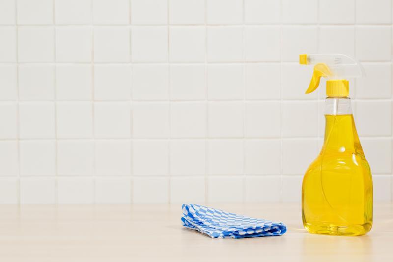 Bottle of yellow cleaning fluid and cleaning cloth