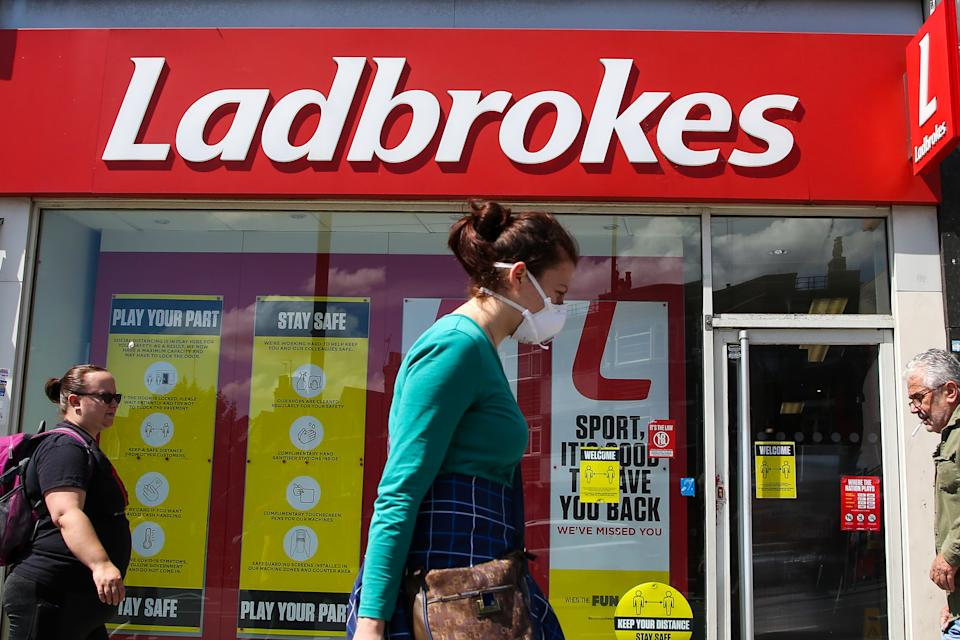 LONDON, UNITED KINGDOM - 2020/06/13: A woman wearing a face mask walks past a branch of Ladbrokes in London. (Photo by Dinendra Haria/SOPA Images/LightRocket via Getty Images)