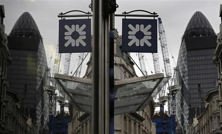 A logo of the Royal Bank of Scotland (RBS) is reflected in the window of a branch office in London