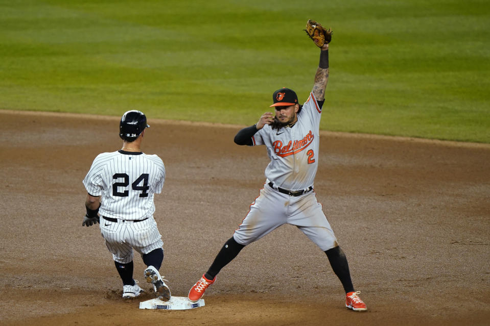 Baltimore Orioles shortstop Freddy Galvis (2) reaches for the throw from the outfield as New York Yankees' Gary Sanchez pulls into second with a double during the sixth inning of a baseball game Wednesday, April 7, 2021, at Yankee Stadium in New York. (AP Photo/Kathy Willens)
