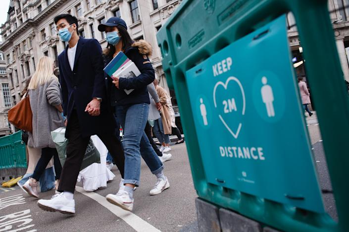 A couple wearing face masks cross Oxford Circus, past a social distancing notice, in London, England, on October 16, 2020. London is to be placed under 'Tier 2' coronavirus lockdown measures from midnight tonight, meaning 'high' alert for covid-19. Most notably the change will introduce a ban on people from different households from mixing anywhere indoors, prompting particular concern within the already badly-affected hospitality industry. (Photo by David Cliff/NurPhoto via Getty Images)