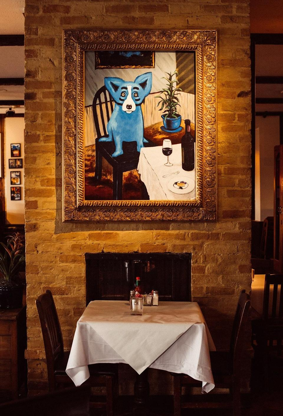 """<p><strong>What were your first impressions when you arrived?</strong> From a distance, this cafe looks fairly nondescript, but the approach reveals a couple of sculptures—including a couple of big, colorful dogs that hint at a more esoteric situation inside. The blue dog in question is the mascot and talismanic subject of revered late local artist George Rodrigue, whose work can be seen all across the state, especially in <a href=""""https://www.cntraveler.com/destinations/new-orleans?mbid=synd_yahoo_rss"""" rel=""""nofollow noopener"""" target=""""_blank"""" data-ylk=""""slk:New Orleans"""" class=""""link rapid-noclick-resp"""">New Orleans</a> and here in Lafayette. As you might imagine, the interior is a shrine to his oeuvre, with dozens of original paintings and prints, and more playful dog portraits than are perhaps collected anywhere. It's like eating in a museum dedicated to one man.</p> <p><strong>What's the crowd like?</strong> Rodrigue's art is incredibly accessible, and loved by kids and adults alike, so there's a good <a href=""""https://www.cntraveler.com/gallery/things-to-do-in-new-orleans-with-kids-that-are-fun-for-you-too?mbid=synd_yahoo_rss"""" rel=""""nofollow noopener"""" target=""""_blank"""" data-ylk=""""slk:showing of families"""" class=""""link rapid-noclick-resp"""">showing of families</a>. His art also hangs in some of the region's most elevated galleries, and so there's also an <a href=""""https://www.cntraveler.com/gallery/best-museums-in-new-orleans?mbid=synd_yahoo_rss"""" rel=""""nofollow noopener"""" target=""""_blank"""" data-ylk=""""slk:arty crowd"""" class=""""link rapid-noclick-resp"""">arty crowd</a> that passes through to pay their respects while chowing on some classic Louisiana cuisine. It makes for a casually convivial ambience either way.</p> <p><strong>What should we be drinking?</strong> The cocktails are unswervingly classic, with takes on local libations such as a Hurricane that's a mile above the same drink on Bourbon Street and a French 75 and others that use tasty southern gins. The wine and beer selection i"""