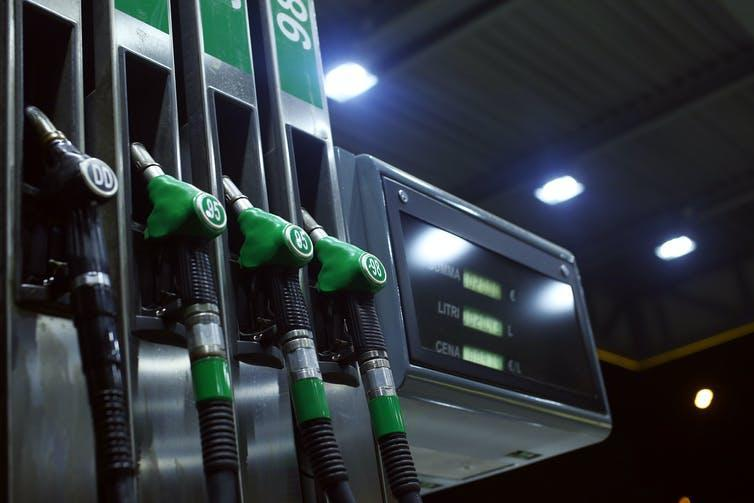 A row of petrol pumps on a station forecourt at night.