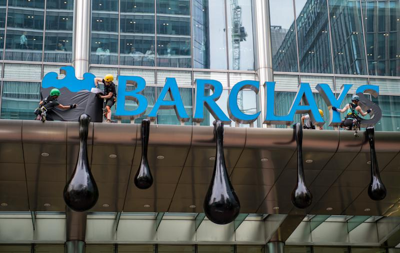 LONDON, ENGLAND - JULY 19: Greenpeace activists redress the main entrance in an oil drip effects as they scale Barclays bank headquaters in Canary Wharf in protest over the bank's refusal to stop funding pipelines that take oil from Canada's tar sands to market in the USA and Asia on July 19, 2018 in London, England. Activists scaled the entrance this morning to redress the headquaters sign in an oil drip effect as well as others entering the building dressed as bankers whilst playing recorded messages from Barclays customers that are in opposition to the bank's funding of the tar sands pipelines. (Photo by Chris J Ratcliffe/Getty Images)