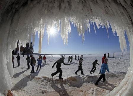 Sightseers look at icicles at the mouth of a sea cave of the Apostle Islands National Lakeshore of Lake Superior near Cornucopia, Wisconsin February 14, 2014. REUTERS/Eric Miller