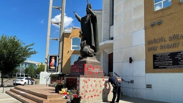 A statue of Pope John Paul II, who was elected as Pope in 1978, located outside an Edmonton church was painted red Saturday night, police say. (Tricia Kindleman/CBC - image credit)