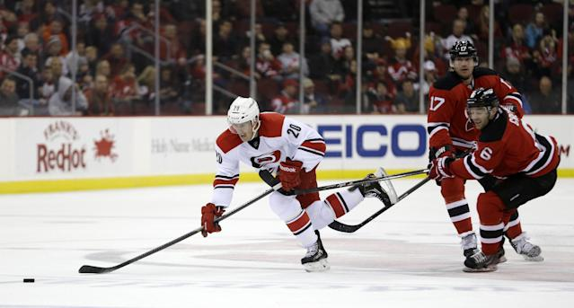 Carolina Hurricanes center Riley Nash (20) skates by New Jersey Devils' Andy Greene (6) and Michael Ryder (17) during the first period of an NHL hockey game, Wednesday, Nov. 27, 2013, in Newark, N.J. (AP Photo/Julio Cortez)