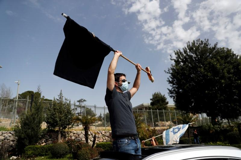 Israeli man waves a black flag during a demonstration against PM Netanyahu's caretaker government, in Jerusalem