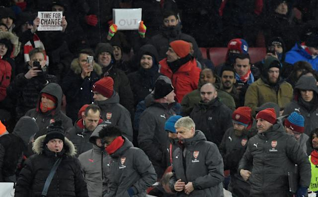 """Soccer Football - Premier League - Arsenal vs Manchester City - Emirates Stadium, London, Britain - March 1, 2018 Arsenal manager Arsene Wenger looks dejected at the end of the match as fans hold up banners Action Images via Reuters/Tony O'Brien EDITORIAL USE ONLY. No use with unauthorized audio, video, data, fixture lists, club/league logos or """"live"""" services. Online in-match use limited to 75 images, no video emulation. No use in betting, games or single club/league/player publications. Please contact your account representative for further details."""