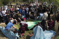 People gather next to the grave during a funeral of Elvira Ignatieva, an English language teacher who was killed at a school shooting on Tuesday, in Kazan, Russia, Wednesday, May 12, 2021. Russian officials say a gunman attacked a school in the city of Kazan and Russian officials say several people have been killed. Officials said the dead in Tuesday's shooting include students, a teacher and a school worker. Authorities also say over 20 others have been hospitalised with wounds. (AP Photo/Dmitri Lovetsky)