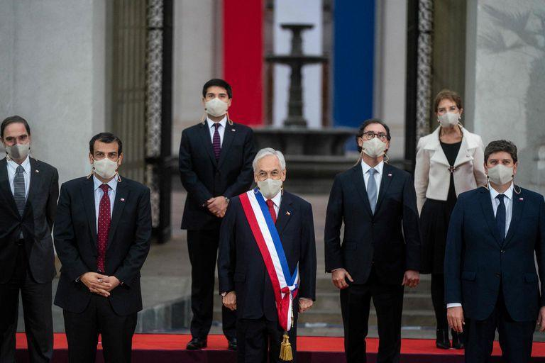 """Handout photo released by the Chilean presidency of President Sebastian Pinera (C) posing for a family picture with cabinet members before his annual message to the nation, in Santiago, on June 1, 2021. (Photo by - / Chilean Presidency / AFP) / RESTRICTED TO EDITORIAL USE - MANDATORY CREDIT """"AFP PHOTO / CHILEAN PRESIDENCY """" - NO MARKETING - NO ADVERTISING CAMPAIGNS - DISTRIBUTED AS A SERVICE TO CLIENTS"""