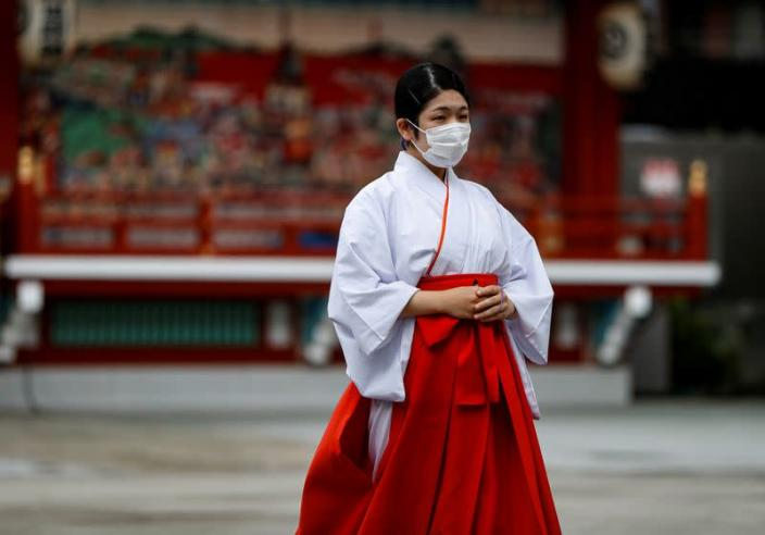 A Shinto maiden wearing a protective face mask walks amid the coronavirus disease (COVID-19) outbreak, in Tokyo
