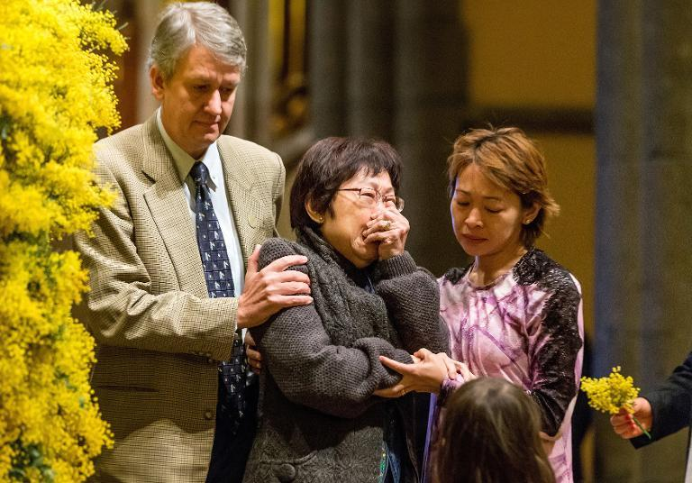 Relatives of victims of downed Flight MH17 grieve at St. Patrick's Cathedral in Melbourne on August 7, 2014 during a national day of mourning