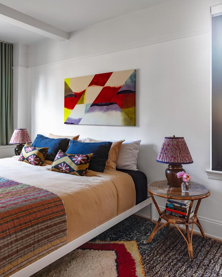 "<div class=""caption""> As is the case with all of the rooms in his home, Joey incorporated various layers into his master bedroom's design. The colors of a Moroccan rug are akin to those in the bedding and lamp shades, which ""have a bit of green in them to match the drapes,"" he says. </div>"