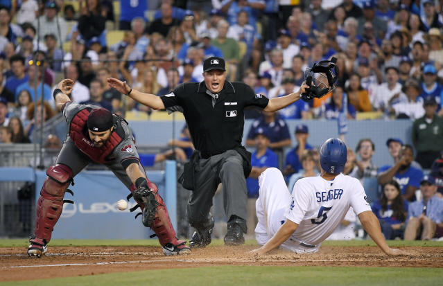 Los Angeles Dodgers' Corey Seager, right, scores on a sacrifice bunt by Kenta Maeda, of Japan, as Arizona Diamondbacks catcher Alex Avila, left, takes the throw and home plate umpire Cory Blaser, center, makes the call during the fourth inning of a baseball game Saturday, Aug. 10, 2019, in Los Angeles. (AP Photo/Mark J. Terrill)
