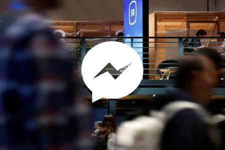 FILE PHOTO - Attendees walk past a Facebook Messenger logo during Facebook Inc's annual F8 developers conference in San Jose, California, U.S. May 1, 2018. REUTERS/Stephen Lam