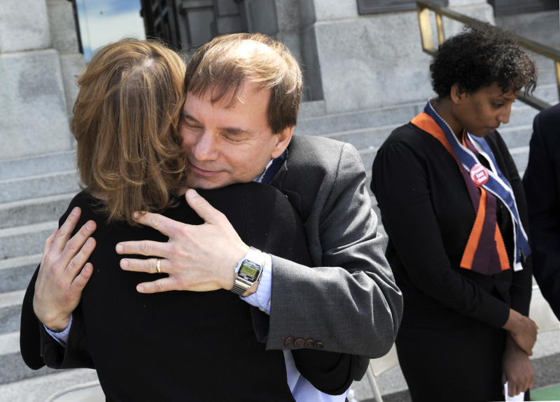 FILE - In this April 20, 2009 file photo, Tom Mauser, father of slain Columbine High School student Daniel Mauser, hugs Lori Haas, mother of Emily Haas, who was wounded in the Virginia Tech shooting, at a Columbine Remembrance and Rededication ceremony at the Capitol building in Denver on the 10th anniversary of the school attack. At far right is Lily Habtu, a Virginia Tech student who was shot three times in the Virginia Tech attack. The year after Columbine, Mauser helped lead an initiative to require background checks for all firearms buyers at state gun shows, a move that didn't prevent accused Aurora shooter James Holmes from acquiring his arsenal. (AP Photo/Chris Schneider)