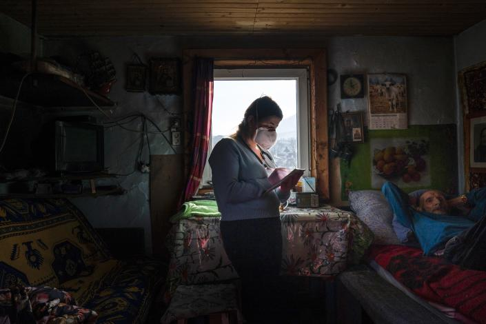 Dr. Viktoria Mahnych, wearing face mask against coronavirus, writes down in her notebook while visiting an elderly patient with COVID-19 in Iltsi village, Ivano-Frankivsk region of Western Ukraine, Wednesday, Jan. 6, 2021. Ukraine is struggling to contain the coronavirus pandemic that has inundated its overburdened medical system, as Dr. Viktoria Mahnych goes door to door providing much needed help to patients. (AP Photo/Evgeniy Maloletka)