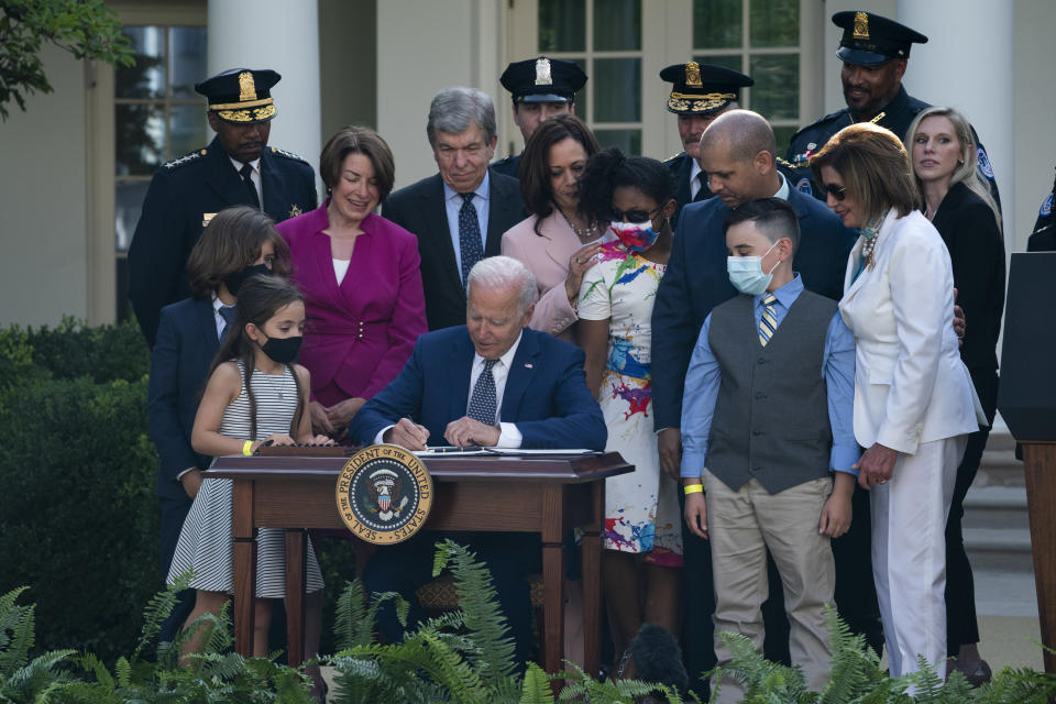 President Joe Biden signs a bill that awards Congressional gold medals to law enforcement officers that protected members on Congress at the Capitol during the Jan. 6 riots, in the Rose Garden of the White House, Thursday, Aug. 5, 2021, in Washington. (AP Photo/Evan Vucci)