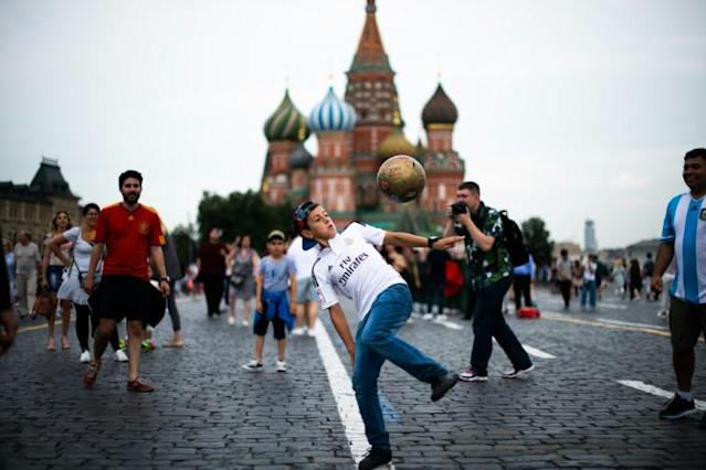 A football fan controls a ball at the Red Square in Moscow on on the eve of the Russia 2018 World Cup final football match between France and Croatia (AFP Photo/Jewel SAMAD)