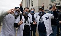 Fans pose in front of Yankee Stadium in New York on Opening Day