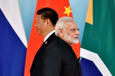 FILE PHOTO: Chinese President Xi Jinping (L) and Indian Prime Minister Narendra Modi attend the group photo session during the BRICS Summit in Xiamen