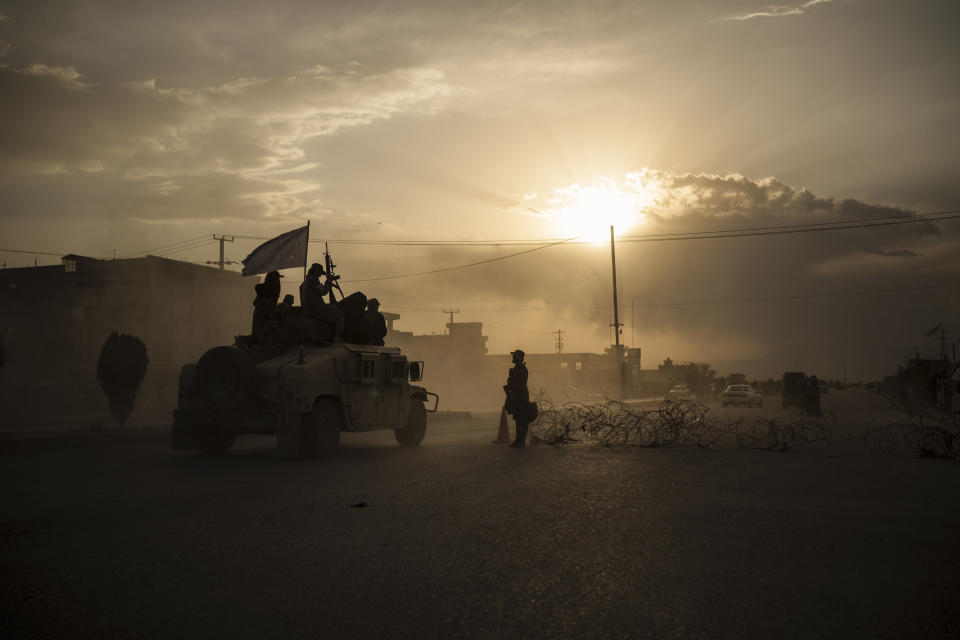 Taliban fighters ride atop a Humvee on the way to detain Afghans involved in a street fight in Kabul, Afghanistan, Tuesday, Sept. 21, 2021. The Taliban are shifting from being warriors to an urban police force. (AP Photo/Felipe Dana)