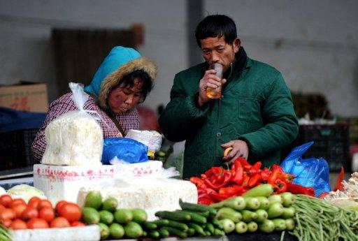 Vendors wait for customers at a vegetable market in Hefei, east China's Anhui province, last month. China's inflation rate edged up in March from the previous month, according to official data, as bad weather pushed up food prices and authorities raised the price of fuel