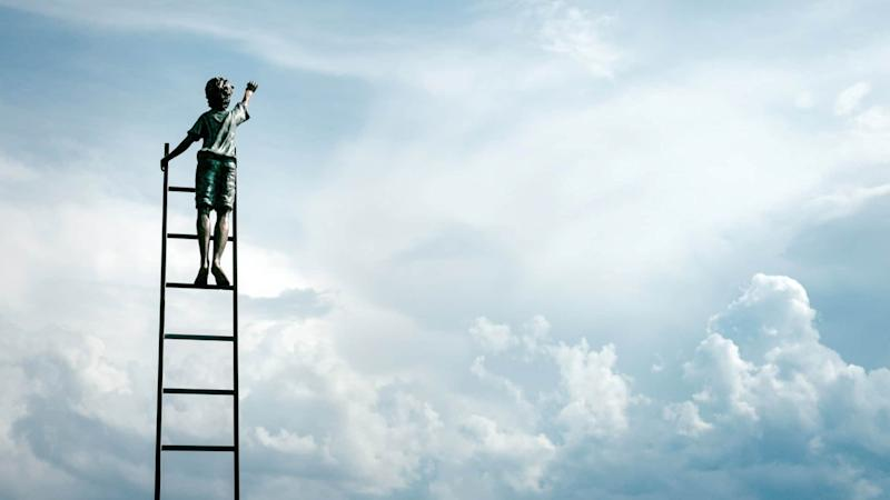 boy standing on ladder against the backdrop of a cloudy sky