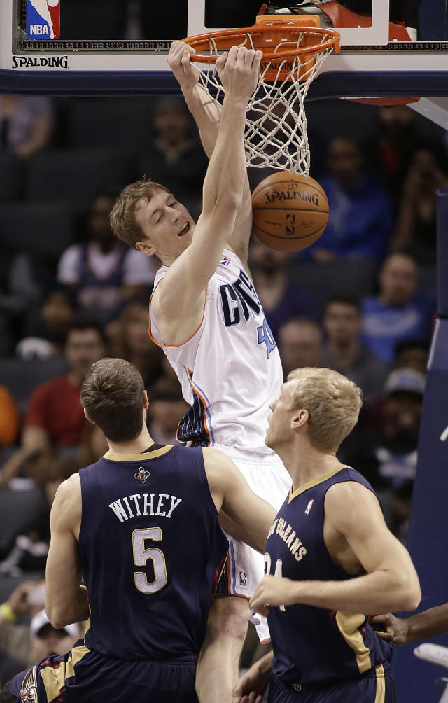 Charlotte Bobcats' Cody Zeller hangs frp, the rim after dunking over New Orleans Pelicans' Jeff Withey, left, and Greg Stiemsma during the first half of an NBA basketball game in Charlotte, N.C., Friday, Feb. 21, 2014. (AP Photo/Bob Leverone)
