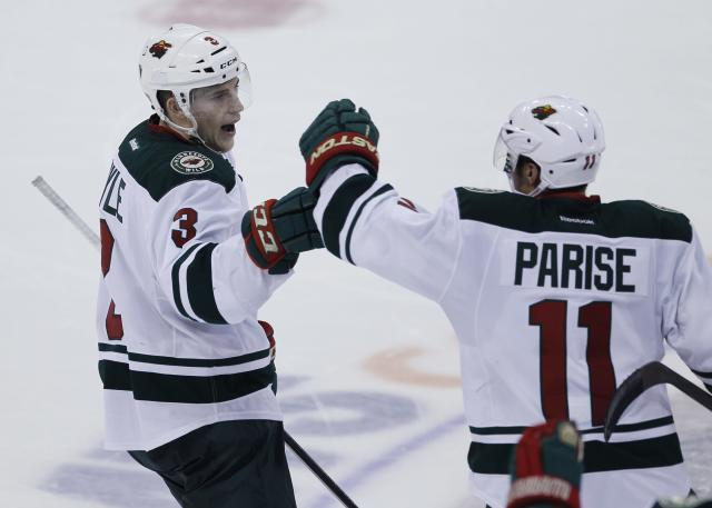 Minnesota Wild's Charlie Coyle (3) and Zach Parise (11) celebrate Coyle's shootout goal for the win over the Winnipeg Jets in an NHL game in Winnipeg, Manitoba, Saturday, Nov. 23, 2013. (AP Photo/The Canadian Press, John Woods)