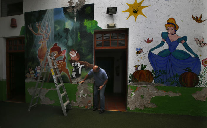 School director Salvador Corral works on restoration projects at La casa del Colibri kindergarten, which remains closed due to the new cornavirus pandemic, in Mexico City, Tuesday, April 20, 2021. The Mexican government began giving teachers in five other states the single-dose CanSino COVID-19 vaccine to speed up their return to the classroom before the end of the school year in July. (AP Photo/Marco Ugarte)
