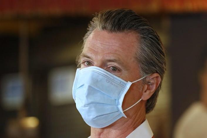 California Gov. Gavin Newsom, wears a face mask as he answers a reporter's question during his visit to the Queen Sheba Ethiopian Cuisine restaurant, in Sacramento, Calif., Friday, June 19, 2020. Newsom visited the restaurant that is participating in the Great Plates Delivered program that provides meals to older adults who are at-risk to COVID-19. (AP Photo/Rich Pedroncelli, Pool)