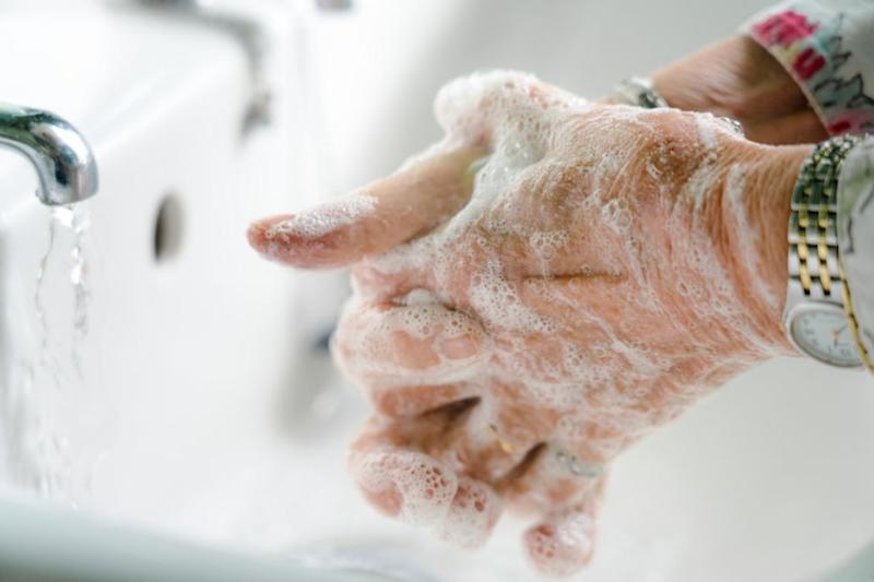 Close-up of an elderly woman's hands as she carefully washes them with soap in a bathroom sink.
