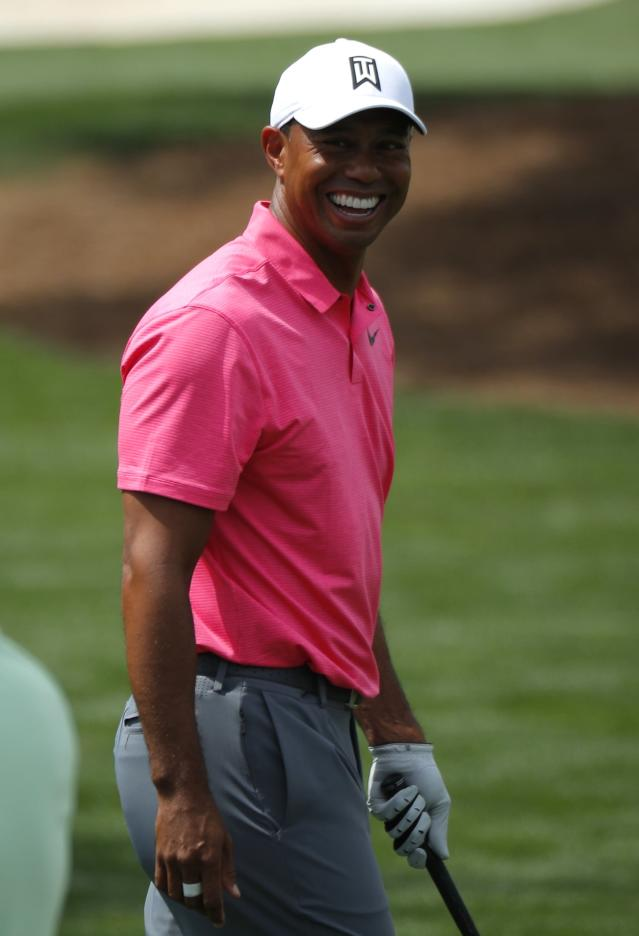 Tiger Woods of the U.S. smiles as he arrives at the driving range during practice for the 2018 Masters golf tournament at Augusta National Golf Club in Augusta, Georgia, U.S. April 2, 2018. REUTERS/Brian Snyder
