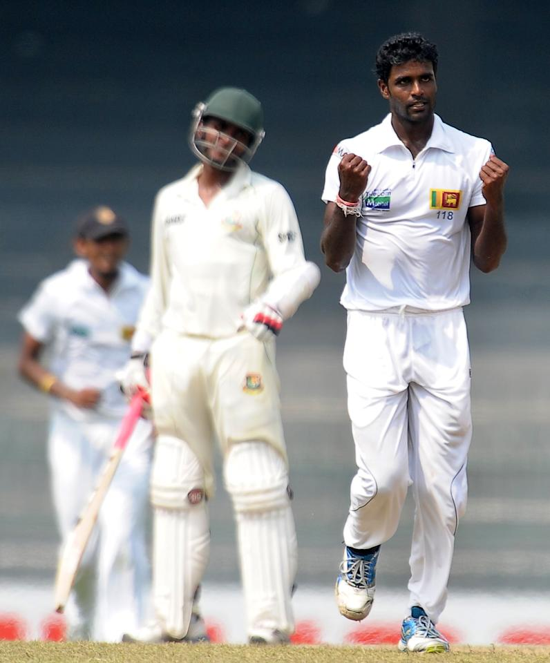 Sri Lankan cricketer Shaminda Eranga (R) celebrates after dismissing unseen Bangladeshi cricketer Tamim Iqbal during the third day of the second Test match between Sri Lanka and Bangladesh at the R. Premadasa Cricket Stadium in Colombo on March 18, 2013. AFP PHOTO/ LAKRUWAN WANNIARACHCHI