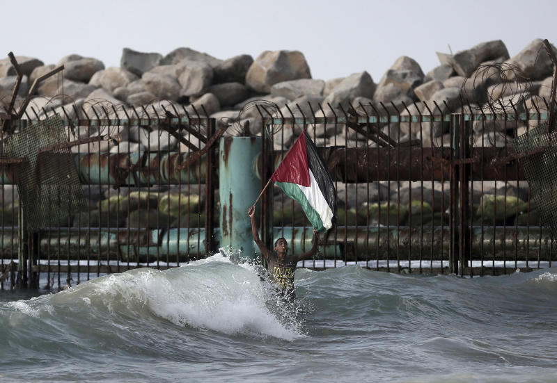 A Palestinian protester holds a national flag as he stands next to the border fence during a protest on the beach at the border with Israel near Beit Lahiya, northern Gaza Strip, Monday, Oct. 8, 2018. (AP Photo/Khalil Hamra)