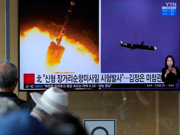 File: People watch a TV screen showing a news programme reporting about North Korea's long-range cruise missiles tests (AP)