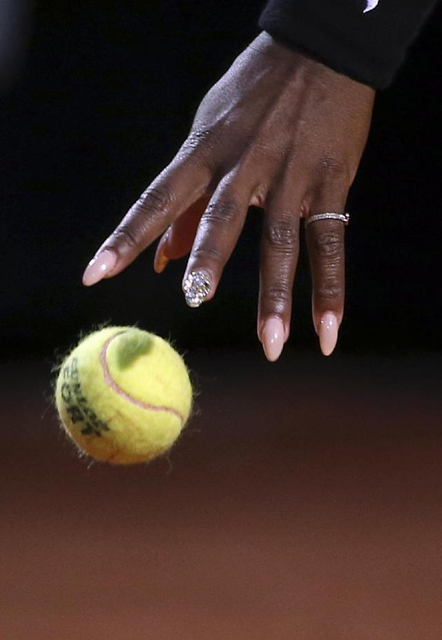 Serena Williams' hand reaches for the ball as she gets ready and serve to China's Shuai Zhang during their match at the Italian open tennis tournament in Rome, Friday, May 16, 2014. (AP Photo/Gregorio Borgia)