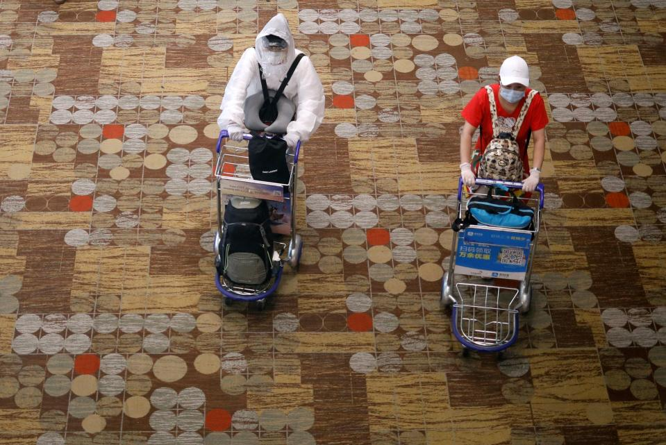 A person wearing a protective gear walks next to someone wearing a face mask and gloves at Changi Airport in Singapore on 30 March, 2020. (PHOTO: Reuters)