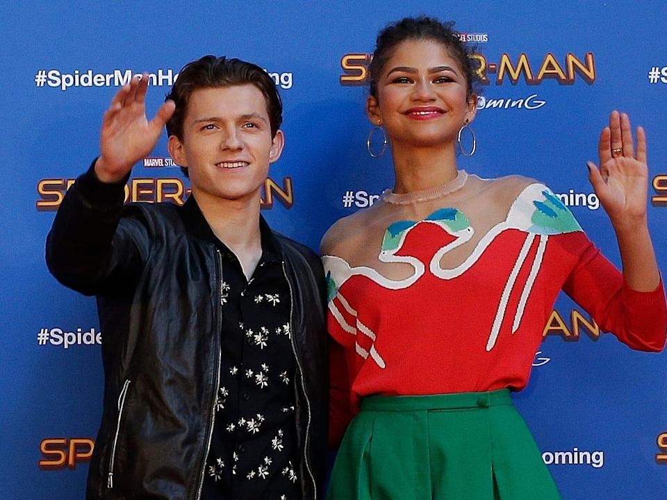 Tom Holland and Zendaya waving at a red carpet in Spain in June 2017.