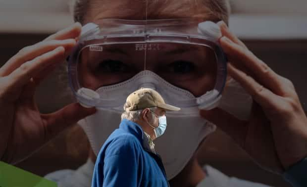 A man wears a protective face mask to help prevent the spread of COVID-19 as he walks past a billboard in Vancouver.