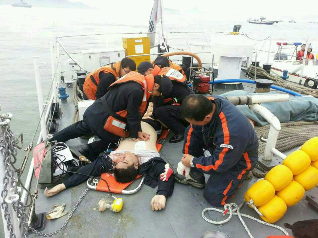 ATTENTION EDITORS - VISUAL COVERAGE OF SCENES OF INJURY OR DEATH An injured passenger who was on a sinking ship, is rescued by South Korean maritime policemen, in the sea off Jindo April 16, 2014 in this picture provided by West Regional Headquarters Korea Coast Guard and released by News1. One person has been found dead in a South Korean ferry that is sinking off the southwest coast, a coast guard official said on Wednesday. The ferry, identified as the Sewol, was carrying about 470 passengers, including 338 high school students and teachers, en route to Jeju island, about 100 km (60 miles) south of the Korean peninsula. REUTERS/West Regional Headquarters Korea Coast Guard/News1 (SOUTH KOREADISASTER LAW - Tags: DISASTER MARITIME CRIME LAW TPX IMAGES OF THE DAY) ATTENTION EDITORS - THIS IMAGE WAS PROVIDED BY A THIRD PARTY. FOR EDITORIAL USE ONLY. NOT FOR SALE FOR MARKETING OR ADVERTISING CAMPAIGNS. THIS PICTURE IS DISTRIBUTED EXACTLY AS RECEIVED BY REUTERS, AS A SERVICE TO CLIENTS. NO SALES. NO ARCHIVES. SOUTH KOREA OUT. NO COMMERCIAL OR EDITORIAL SALES IN SOUTH KOREA