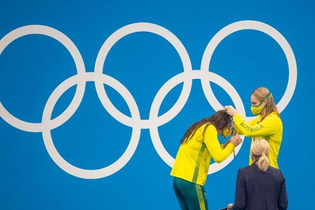 Kaylee McKeown of Australia, left, receives her gold medal in women's 200 meter backstroke from Australia's Emily Seebohm, who won the bronze, on July 31. (Photo: Tim Clayton - Corbis via Getty Images)